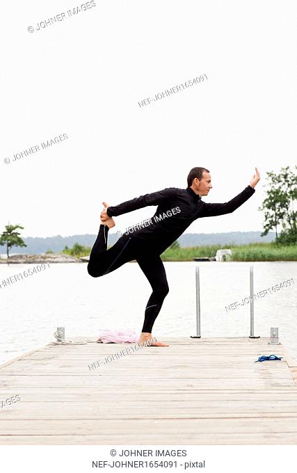 Man practicing yoga on jetty
