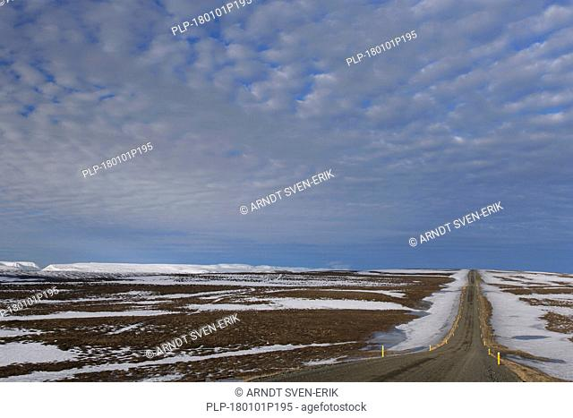 Road leading through the tundra towards the mountain range Lambafjöll / Lambafjoell in winter, Northeastern Region / Norðurland eystra, Iceland