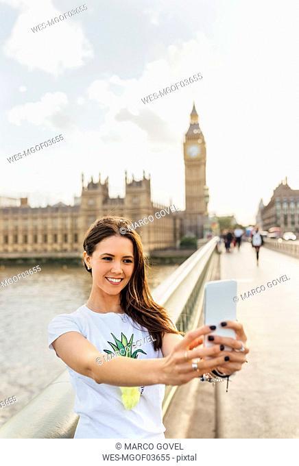 UK, London, beautiful woman taking a selfie on Westminster Bridge