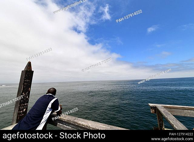 A Namibian looks pensively from the Swakopmund pier onto the Atlantic Ocean, taken on 02.03.2019. Photo: Matthias Toedt / dpa-Zentralbild / ZB / Picture...