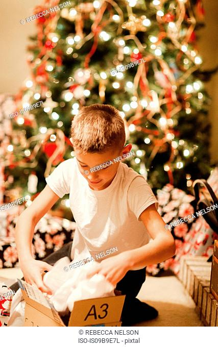 Boy unwrapping gift at Christmas
