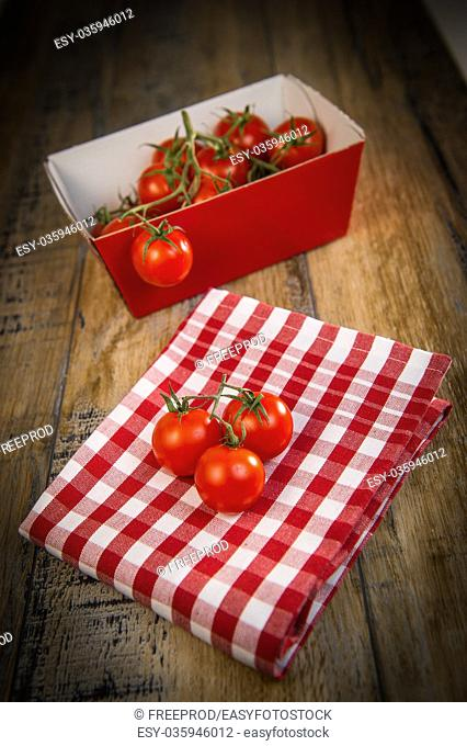 Fresh cherry tomatoes on travel and wooden background, France