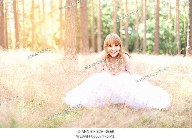 Happy bride wearing white wedding dress sitting on a meadow
