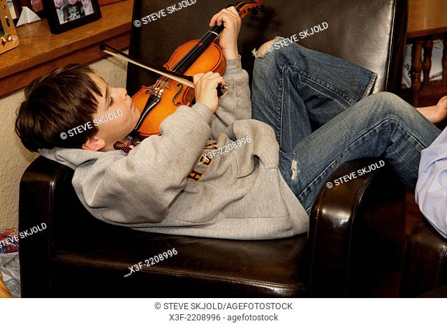 Total relaxation of young violinist practicing in his home. St Paul Minnesota MN USA