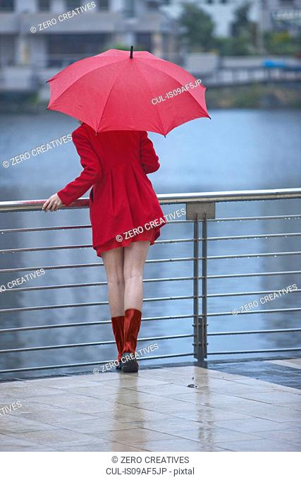 Young woman in red waiting by waterfront