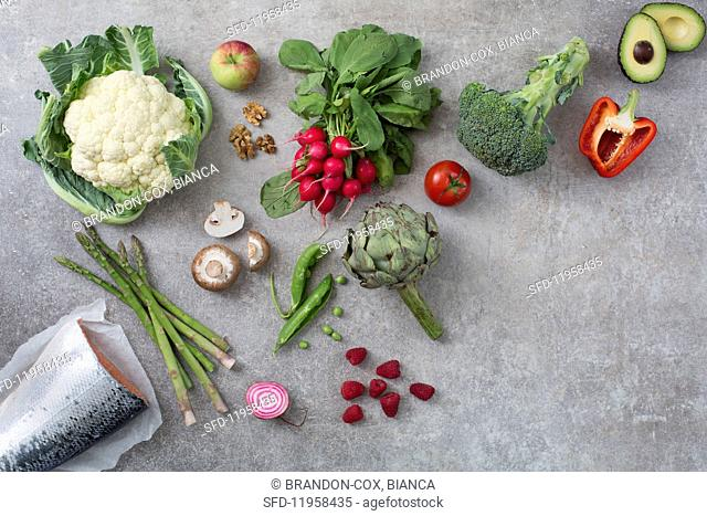 An arrangement of vegetables, fish, berries and nuts