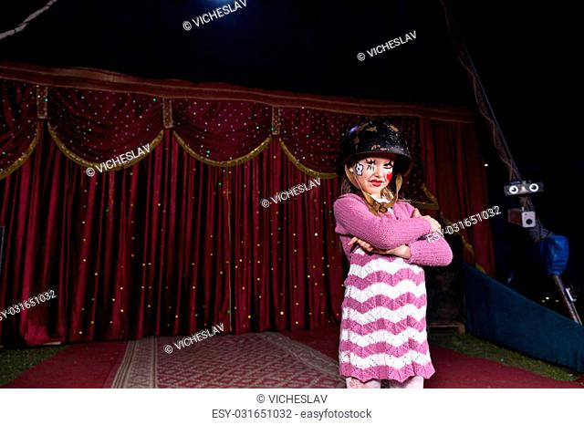 Tough Looking Girl Wearing Combat Helmet and Striped Dress Standing Confidently with Arms Crossed on Stage with Red Curtain