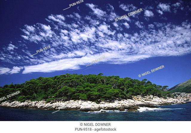 A wide-angle view of Lokrum Island featuring a mackerel sky from a boat just offshore from Dubrovnik Old Town, Dubrovnik