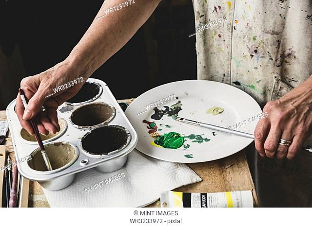 High angle close up of artist mixing green and brown colours on white plate