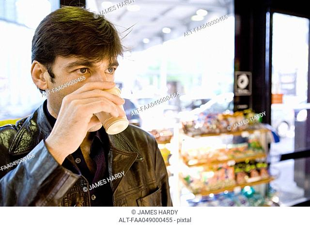 Man drinking coffee in convenience store