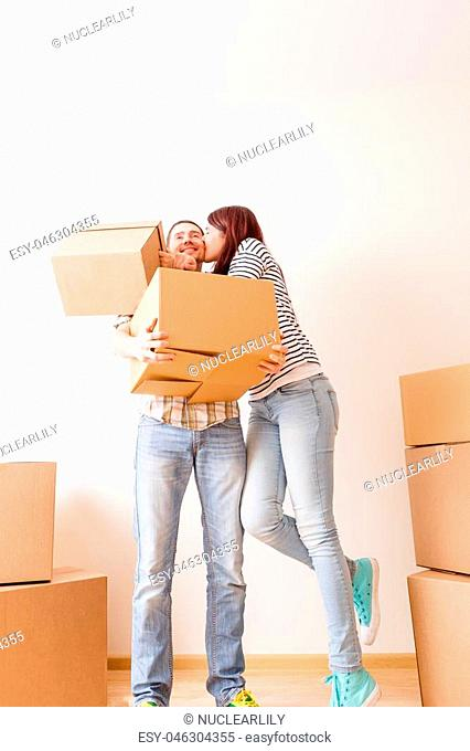 Image of couple in love among cardboard boxes in new apartment