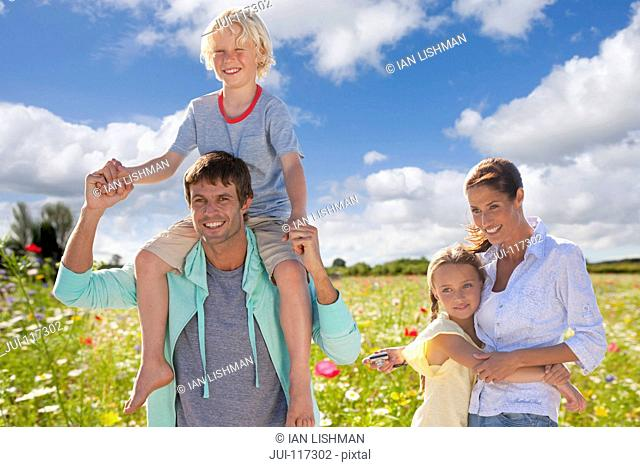 Portrait Of Family On Walk Through Field Of Summer Flowers