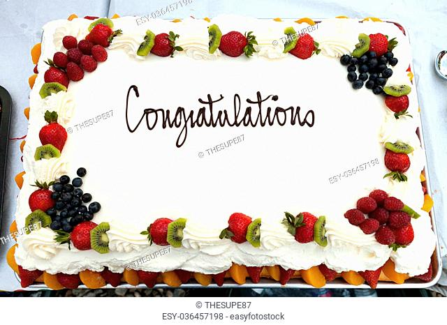 White frosted cake with a fruit border and the message that reads Congratulations