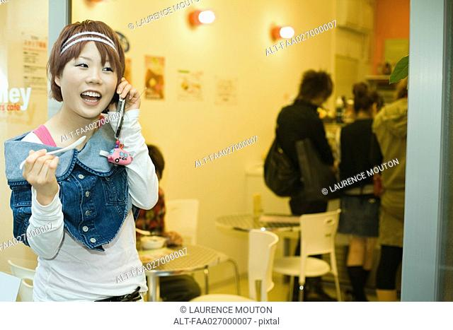 Young woman standing outside restaurant, using cell phone, holding spoon