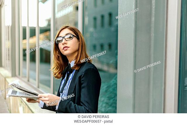Businesswoman standing in front of wall, reading newspaper
