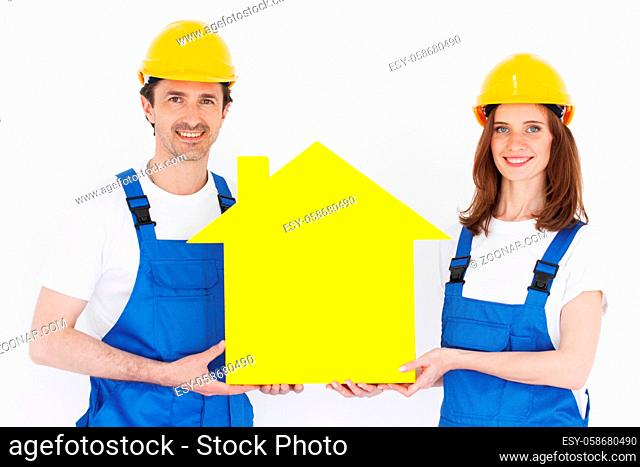 Two happy smiling workers hold yellow house model outdoors at construction site