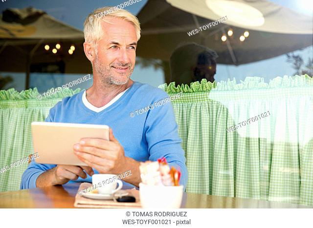 Portrait of smiling man with digital tablet