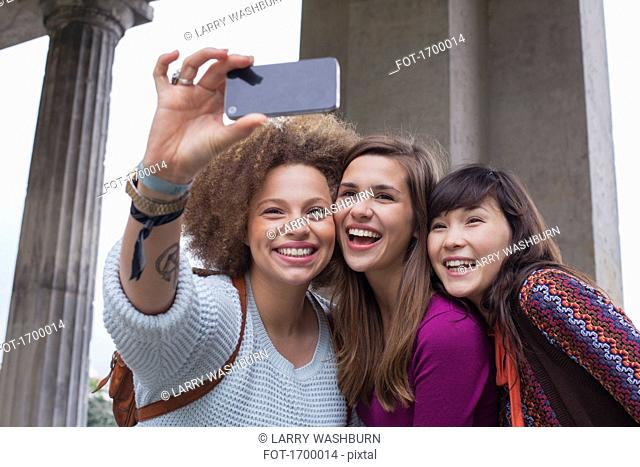 Low angle view of smiling young female friends taking selfie