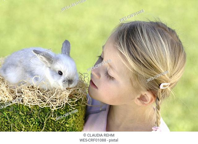 Girl looking at easter bunny, close-up, portrait