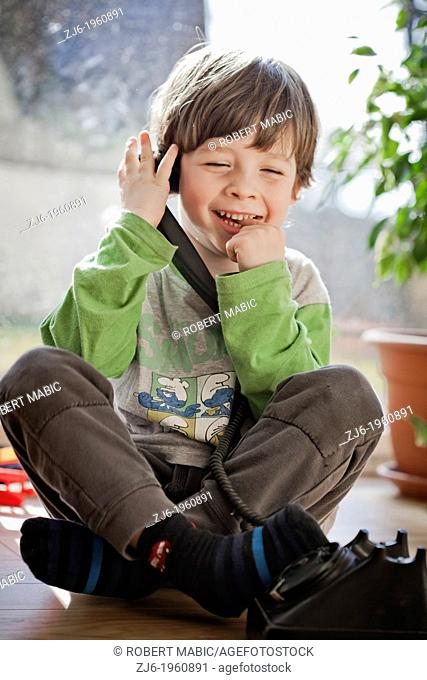 Boy using a retro telephone