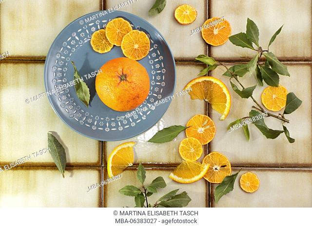 Citrus fruits and leaves on blue plate