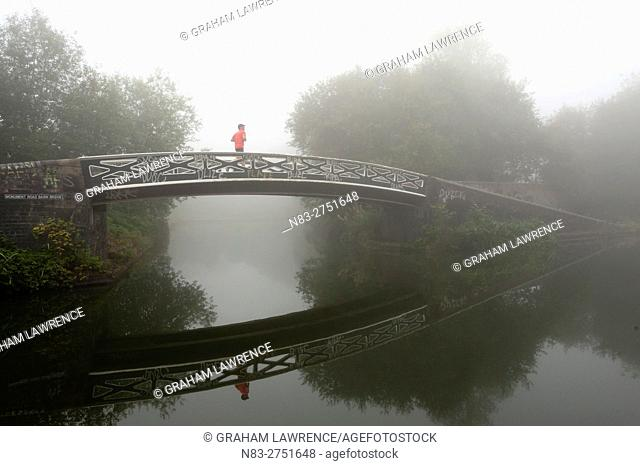 A jogger on a bridge on Birmingham Canal Navigations, (BCN) Birmingham, West Midlands, UK