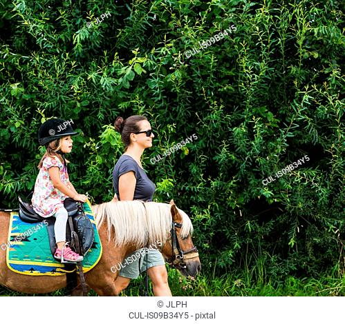 Side view of mother guiding daughter riding horse