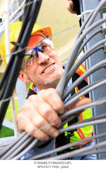 Engineer looking at communications cable distribution panel