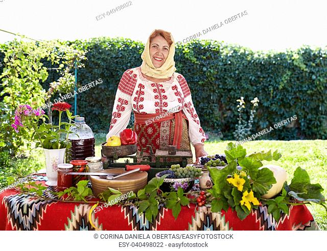 Romanian senior woman dressed in national costume, showing local agricultural products