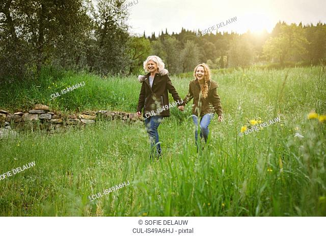 Teenage daughter and mother strolling in field