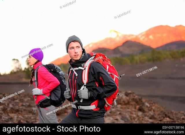 Hiking people on mountain. Hiker couple walking with backpacks outdoors in high altitude. Young man hiker in focus trekking at sunset on volcano Teide, Tenerife
