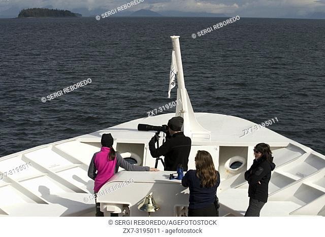 Tourists doing photos to the whales in Safari Endeavour cruise at Five Fingers Lighthouse. Frederick Sound. Stephen's Passage. Petersberg Alaska