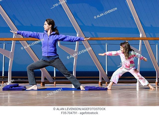 Woman and girl doing yoga on cruise ship