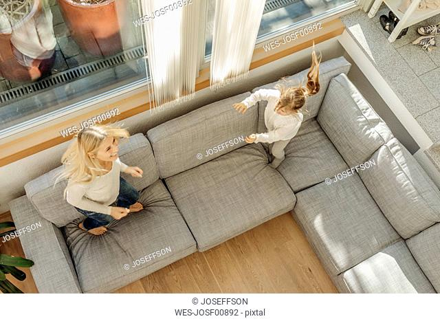 Mature woman and girl at home bouncing on couch