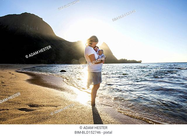 Caucasian mother holding baby in waves on beach