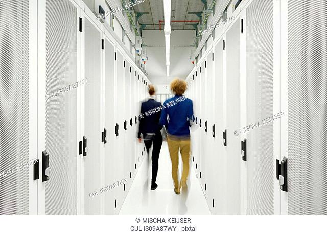 Two employees walking away in data storage room