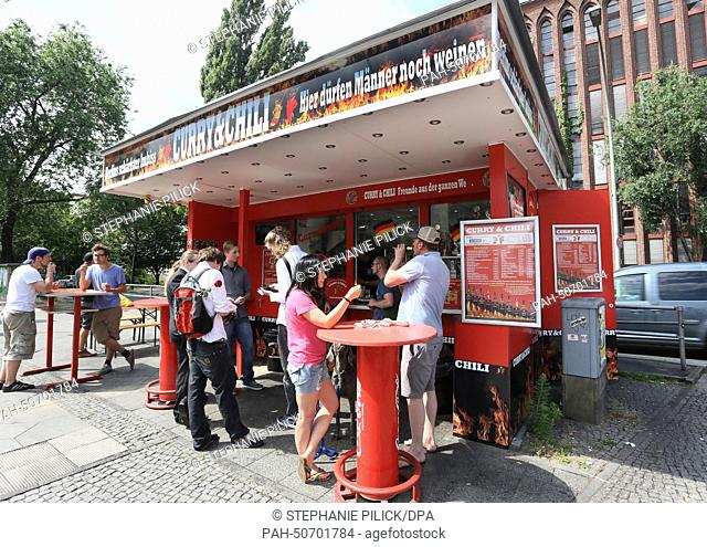 People stand at the snack stand 'Curry & Chily' in Wedding in Berlin, Germany, 07 July 2014. The diner offers curry sausages in varying degrees of spiciness
