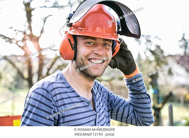 Young man wearing working helmet and ear defenders, portrait