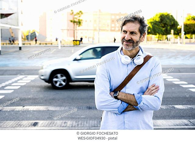 Portrait of smiling mature man with headphones standing at a street