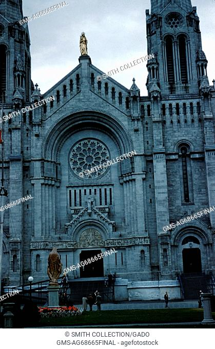 Color photograph of the front of Sainte-Anne-de-Beaupre Cathedral, small group of people standing in the front, Quebec, Canada, 1952