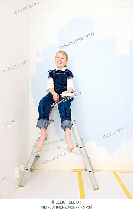 Girl with paint roller sitting on ladder
