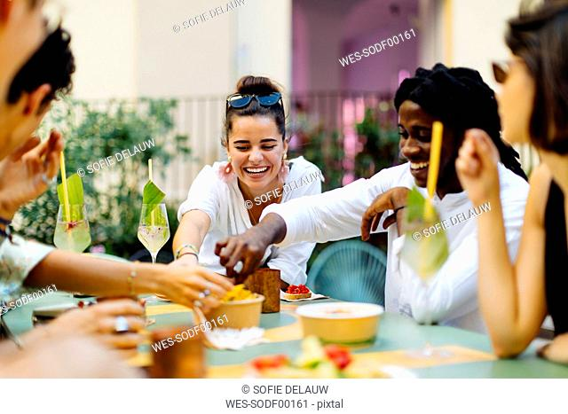 Happy multi-ethnic friends having fun during a party, eating together