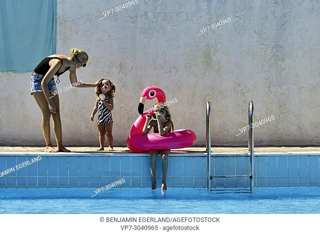 mother caressing little daughter next to pool, other girl enjoying summer vibes with rubber swan. Australian ethnicity