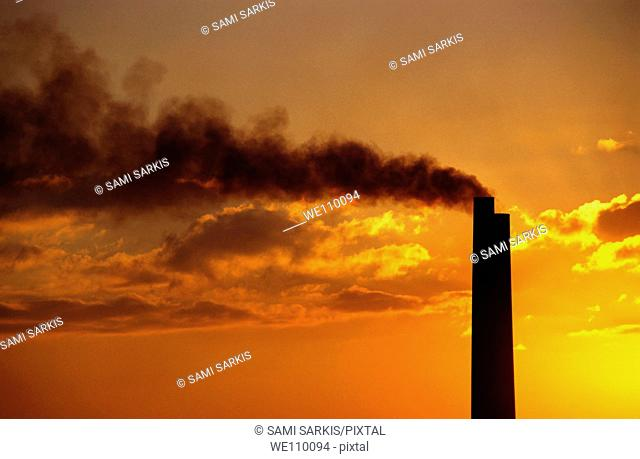 Silhouetted smoking chimney at sunset, Berre, France