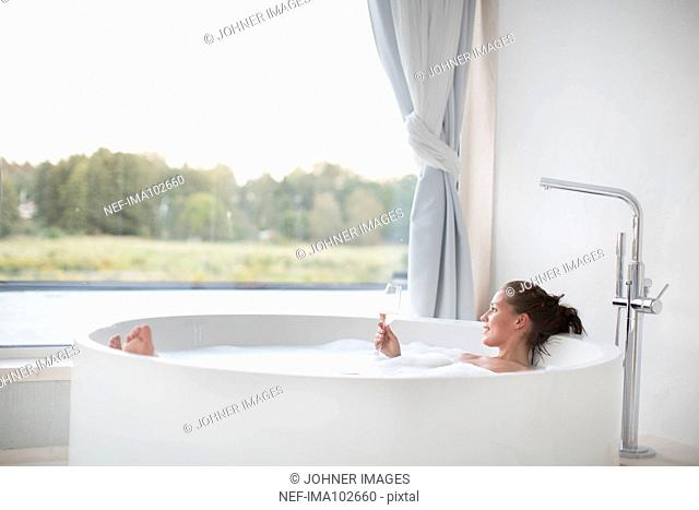 Young woman having bath and drinking wine