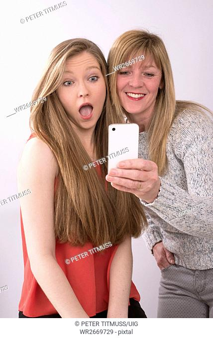 Expressive portrait of mother and daughter using a mobile phone