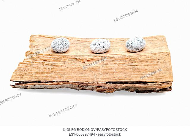 Three stones on a grunge wood isolated on white