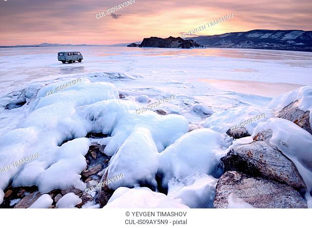 View of off road tourist vehicle and Oltrek Island at sunset, Baikal Lake, Olkhon Island, Siberia, Russia