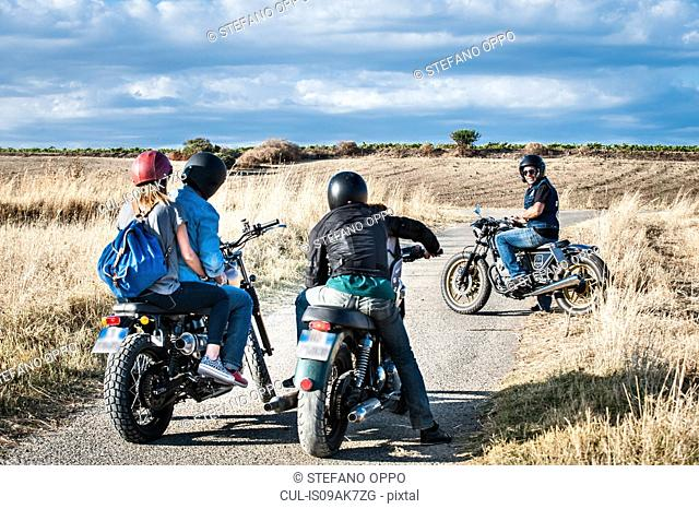 Rear view of four friends chatting on motorcycles on rural road, Cagliari, Sardinia, Italy