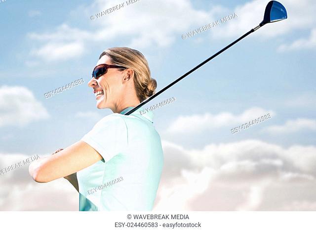 Smiling woman playing golf